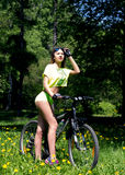 Portrait of pretty young woman with bicycle in a park - outdoor Royalty Free Stock Photos