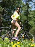 Portrait of pretty young woman with bicycle in a park - outdoor Royalty Free Stock Photography