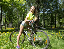 Portrait of pretty young woman with bicycle in a park - outdoor Stock Photography