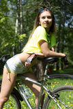Portrait of pretty young woman with bicycle in a park - outdoor Stock Image
