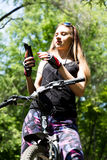 Portrait of pretty young woman with bicycle in a park - outdoor. listening to music on your phone Stock Image
