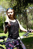 Portrait of pretty young woman with bicycle in a park - outdoor. listening to music on your phone Stock Photos