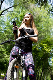 Portrait of pretty young woman with bicycle in a park - outdoor. listening to music on your phone Stock Photography