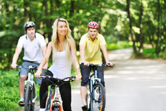 Portrait of pretty young woman with bicycle in a park with two m Stock Photography