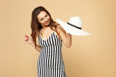 Portrait of pretty young woman in black and white striped dress holding in hand, looking on hat isolated on pastel beige royalty free stock images