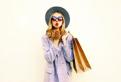Portrait pretty young woman blowing red lips sends air kiss with shopping bags in pink coat, round hat stock photos