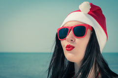Portrait of a pretty young woman  in christmas themed outfit. And red sunglasses on a beach. Toned effect Royalty Free Stock Images
