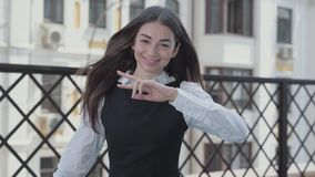 Portrait of a pretty young woman dancing happily on the terrace looking in the camera. Businesswoman received great news. Portrait of a pretty young woman stock video footage