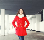Portrait of pretty young woman dressed a red coat outdoors Stock Photo