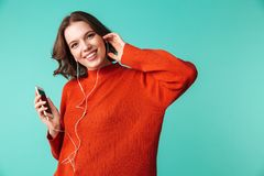 Portrait of a pretty young woman dressed in sweater. Listening to music in earphones isolated over blue background Stock Image