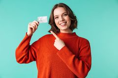 Portrait of a pretty young woman dressed in sweater. Pointing finger at credit card isolated over blue background Royalty Free Stock Photo