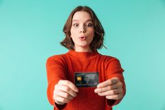 Portrait of a pretty young woman dressed in sweater. Showing credit card isolated over blue background Royalty Free Stock Photography