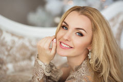 Portrait of pretty young woman in evening dress smiles in Christmas Stock Photos