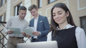 Portrait of pretty young woman working with laptop. Two men on the background looking at her holding documents. Business. Portrait of pretty young woman in the stock footage
