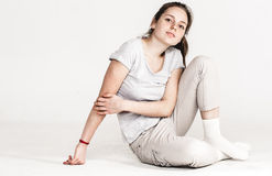 Portrait of a pretty young woman girl sitting on the floor isolated on white Stock Image