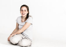 Portrait of a pretty young woman girl sitting on the floor isolated on white Stock Photography
