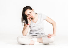 Portrait of a pretty young woman girl sitting on the floor isolated on white Stock Photos
