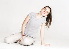 Portrait of a pretty young woman girl sitting on the floor isolated on white Stock Photo