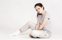 Portrait of a pretty young woman girl sitting on the floor isolated on white Stock Images
