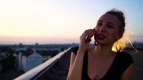 Portrait of pretty young woman with hair band talking on phone on roof at sunset. Outdoor activity of young people. communication, technology, modern gadgets stock video