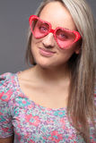 Portrait of a pretty young woman with heart-shape sunglasses stock image
