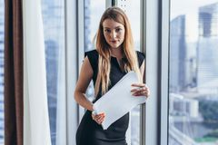 Portrait of pretty young woman holding documents looking at camera standing in office stock photos