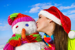 Portrait of a pretty young woman kissing a snowman Royalty Free Stock Image