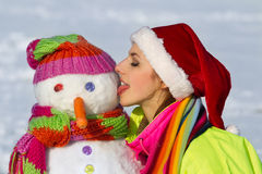 Portrait of a pretty young woman kissing a snowman Stock Photos