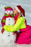 Portrait of a pretty young woman kissing a snowman Royalty Free Stock Photography