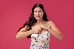 Portrait of a pretty young woman in a light dress standing on pink background in studio. People sincere emotions. Portrait of a young woman in a white dress stock photography