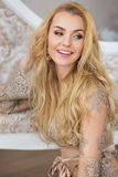 Portrait of pretty young woman with long hair sits and smiles Royalty Free Stock Images