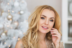 Portrait of pretty young woman with long hair smiles and touches a earring Stock Photography