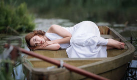 Portrait of pretty young woman lying in the boat on river bank. Stock Photography
