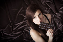 Portrait of pretty young woman nibbling the bar of chocolate Royalty Free Stock Photos