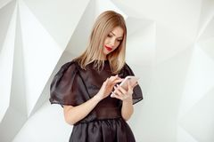 Portrait of pretty young woman with phone on white interior background. stock image