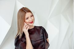 Portrait of pretty young woman with phone on white interior background. stock images