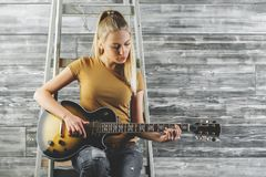 Pretty woman playing the guitar Stock Photography