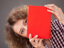 Portrait of a pretty young woman with a red book Royalty Free Stock Images