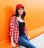 Portrait of pretty young woman in red cap and checkered shirt Royalty Free Stock Images