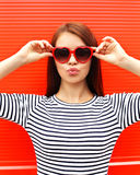 Portrait of pretty young woman in red sunglasses blowing lips Royalty Free Stock Photo