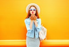 Portrait pretty young woman sends an air kiss on a orange. Background Royalty Free Stock Image