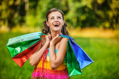 Portrait pretty young woman shopping bags. Portrait pretty young woman standing keeps shoulders shopping bags background summer green park Stock Photography