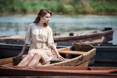 Portrait of pretty young woman sitting in the boat on river bank. Stock Image