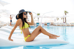 Portrait of a pretty young woman sitting on deckchair outdoors. At the swimming pool Stock Photography