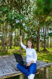 Portrait of pretty young woman sitting on wooden chair and Success gesture in park with legs crossed during summer day while using stock image