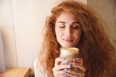 Portrait of a pretty young woman smelling her coffee drink Stock Photography