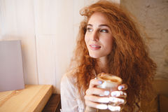 Portrait of a pretty young woman smelling her coffee drink Stock Photos