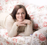 Portrait of pretty young woman smiling laying on sofa Stock Image