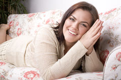 Portrait of pretty young woman smiling laying on sofa Stock Images