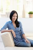 Portrait of pretty young woman on sofa Stock Images